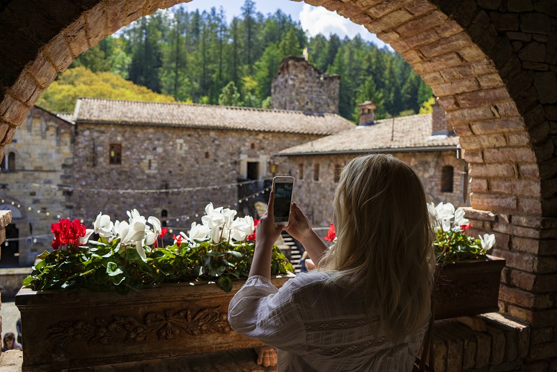 Girl taking a photo with iphone of a scene at a castle photo