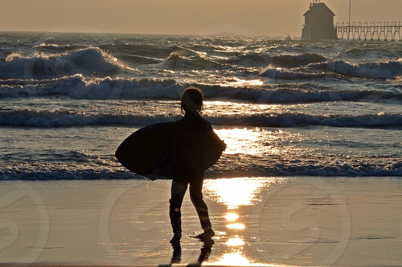 silhouette of a boy surfing on lake Michigan photo