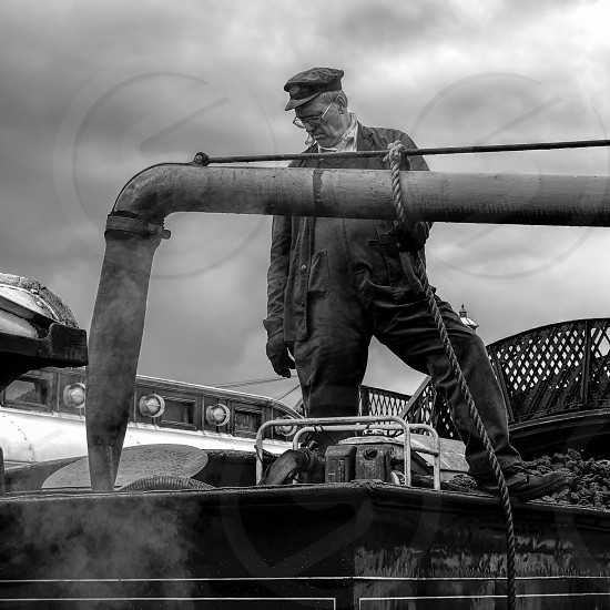SHEFFIELD PARK EAST SUSSEX/UK - SEPTEMBER 8 : C Class Steam Engine taking on water at Sheffield Park station East Sussex on September 8 2013. Unidentified man photo