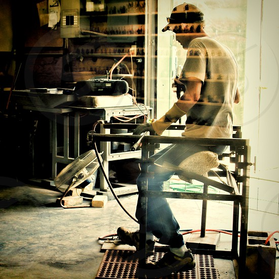 Glassblower at work behind a glass wall. photo