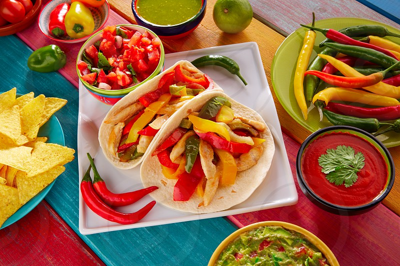 Chicken fajitas tacos mexican food guacamole pico de gallo chili peppes sauces photo