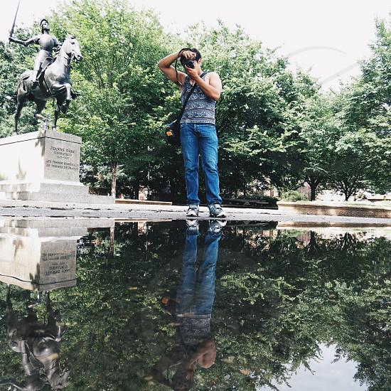 man in grey tank top and blue denim jeans using black dslr camera photo