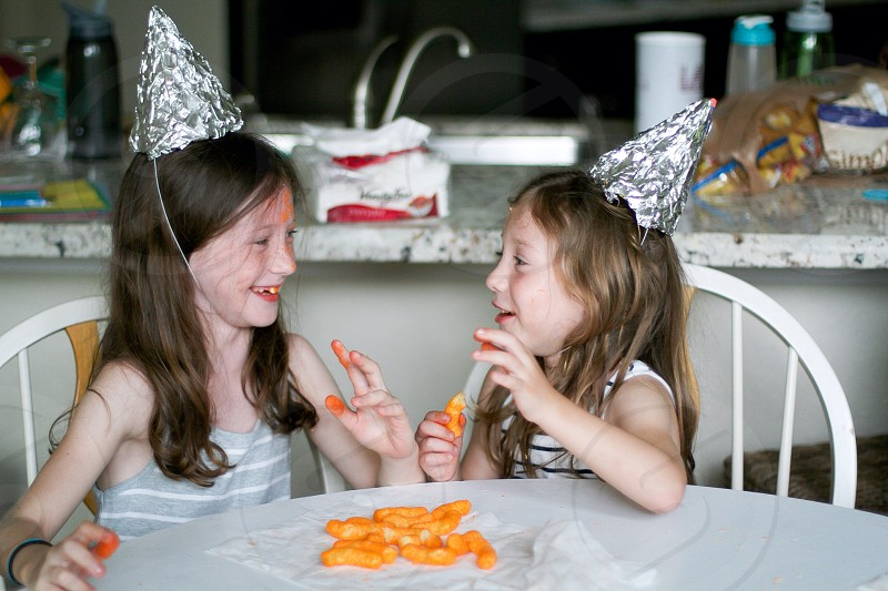 two girls wearing silver party hat and eating cheesy curls photo