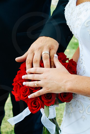 woman wearing gold wedding band with diamond and holding rose bouquet photo
