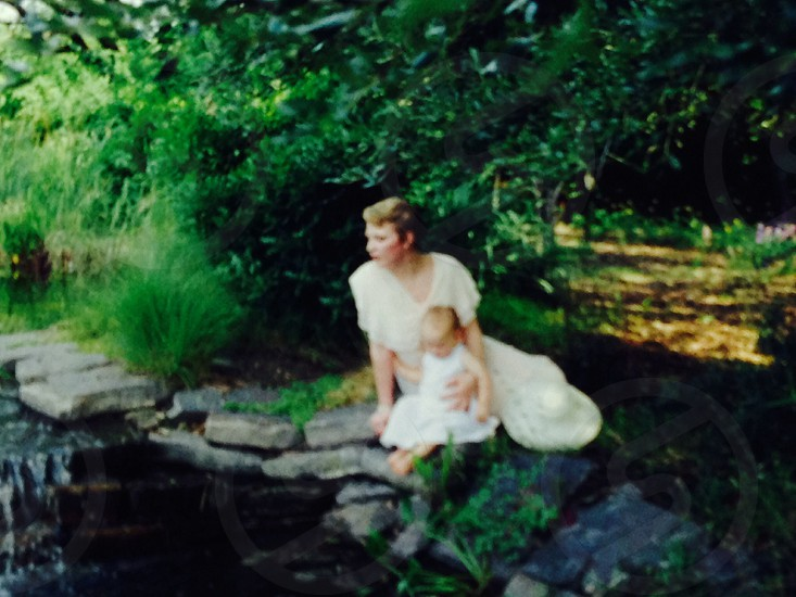 woman in white dress sitting near pond surrounded by green leafed trees photo