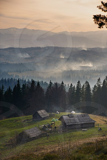 Sunrise above the high mountain foggy valley with old wooden houses on a hill photo