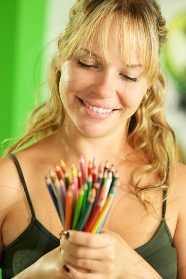 smiling happy pencil pencils woman art artist adult 20s bunch caucasian closeup color colorful colour concept craft create creative creativity draw drawing female girl group hand hands hobby holding idea image imagination indoor inspiration job leisure looking object objects occupation one painter painting people person profession vision white work young photo