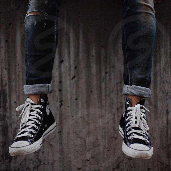 person wearing blue denim ragged jeans and black hi cut converse sneakers photo