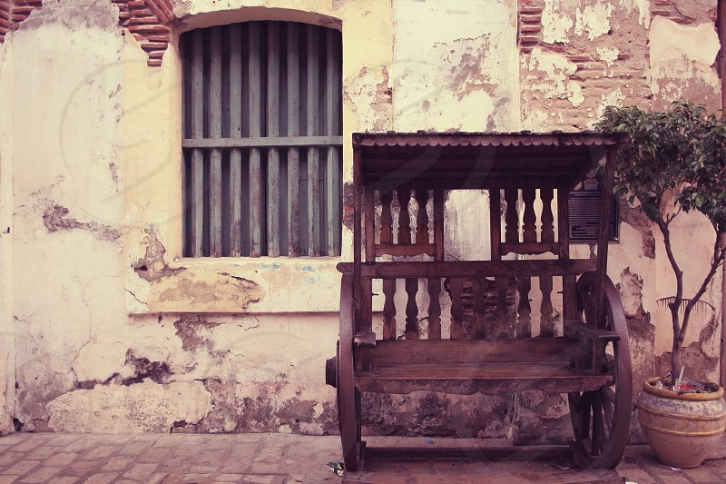 Vintage wood cart by a white stucco building photo
