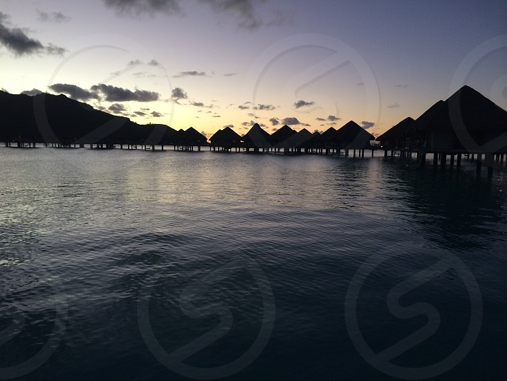 Bungalows over water with sunset photo