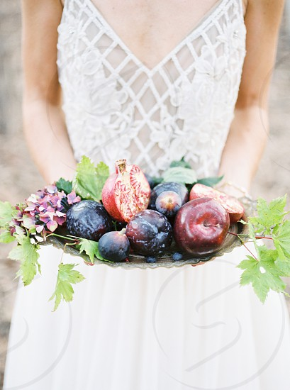 A bride holding a plate of fruit. photo