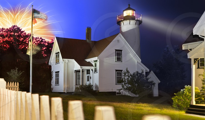 fireworks behind white and black house near lighthouse photo