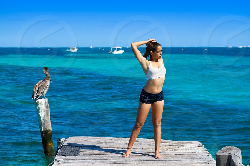 Latin athlete woman stretching in Caribbean beach pier photo