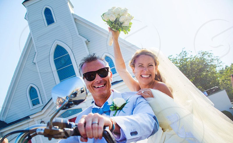 newlywed couple on motorcycle in front of church photo