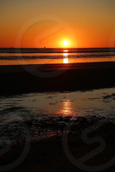 Sunset Crosby near Liverpool UK bright orange sky beach shore photo