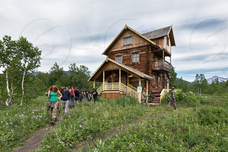 NALYCHEVO KAMCHATKA PENINSULA RUSSIA - JULY 12 2014: View of building of Museum of Nature Park Nalychevo environmental education center named after V. Semenov and a group of tourists near museum. photo