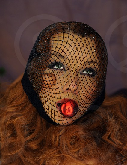 woman with black net over face with red light in mouth photo