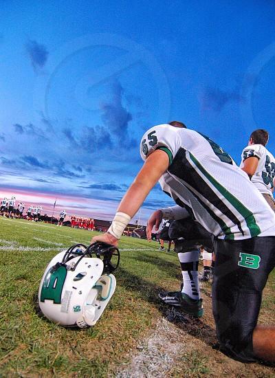 Football no face portrait high school  kneeling helmet field photo