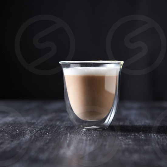 A glass cup of hot flavored cappuccino presented on a black wooden table with copy space. photo