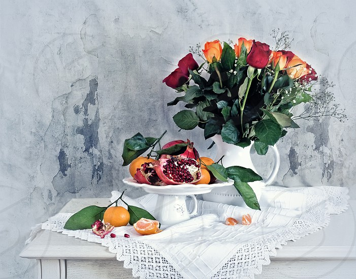 Still life with red pomegranate orange tangerines and color roses photo