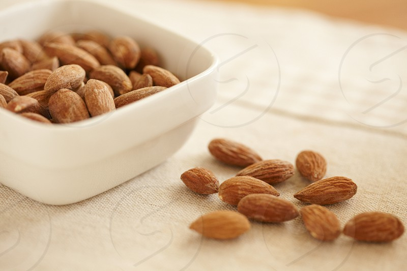 almond food brown white beige nuts bowl natural light table photo