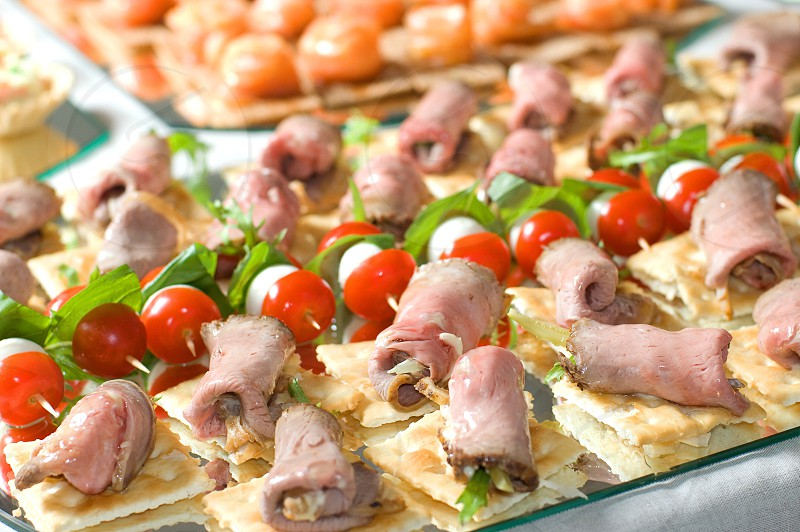 rolled meat on crackers with vegetable shish kabobs photo