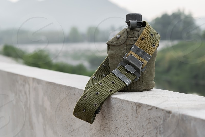 Army water canteen with a Cartridge belt on bridge bar at riverside. photo