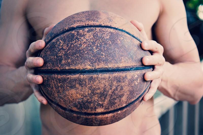 Man holding dirty baseball showing grunge texture. photo