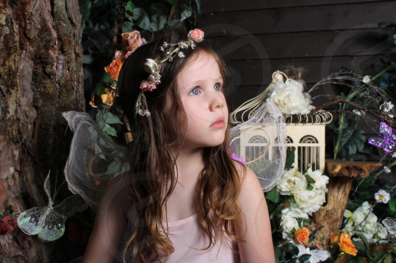 fairy portrait of a child in fairy costume. magical image capturing the essence of childhood imagination and wonder. Sitting like a pixie in a wonderland garde photo