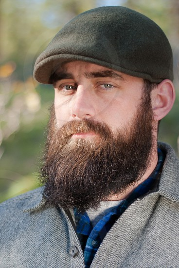 Bearded man with cap in the outdoors facing camera photo