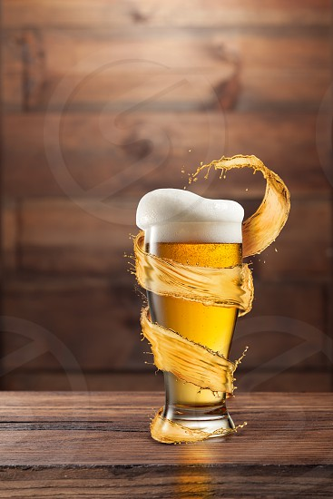 A glass of cold beer with drops and froth around a splash on a dark wooden background with copy space. photo