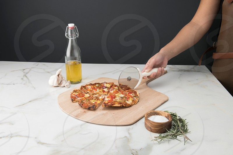 Lifestyle food photography for pizza slicer shot on a cutting board and marble background photo