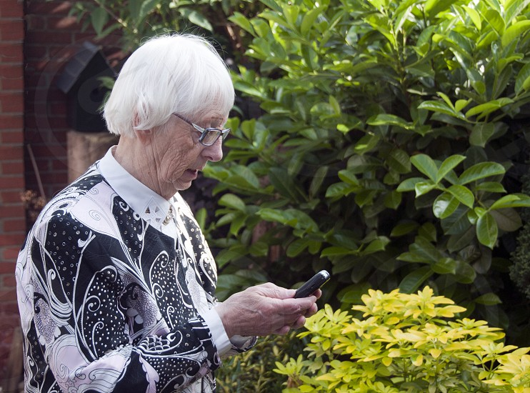 grandmother with mobile phone making a sms photo