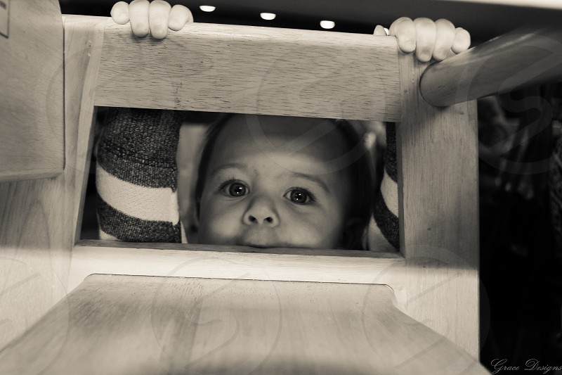 Young boy peering through the high chair. photo
