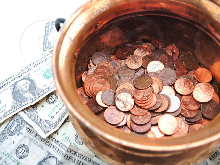 round copper bowl of pennies on us one dollar bills on white table photo