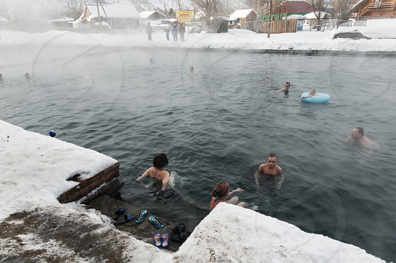 KAMCHATKA PENINSULA RUSSIA - MARCH 8 2013: A group of people relaxing in the winter in the public pool with natural thermal mineral water on a cloudy day. Eurasia Russian Far East Kamchatsky Krai Esso Village. photo