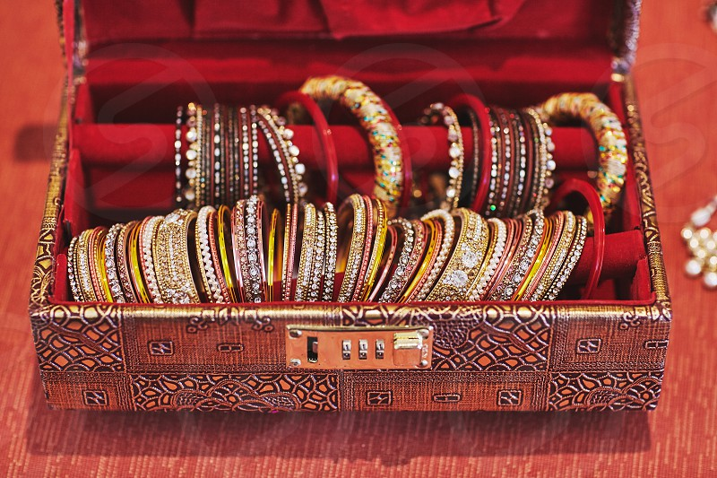 A collection of glitter and shiny bracelets or bangles in various jewely decoration in the luxury red velvet box for indian bride photo