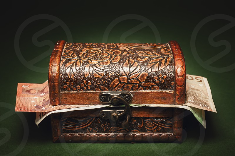 Studio conceptual image wooden decorated vintage suitcase full of euro banknotes.  photo