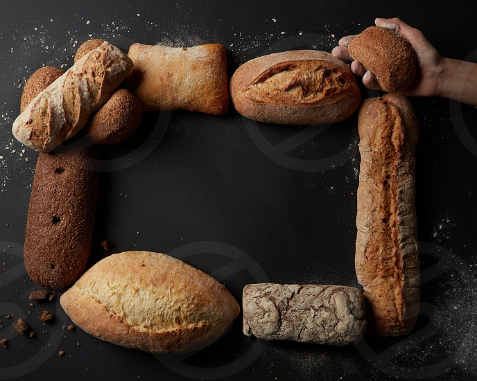 Top view of frame of breads over black. Woman's hand holding bun over this frame. Copy space for your ideas emotions etc. Baking and cooking concept background. photo