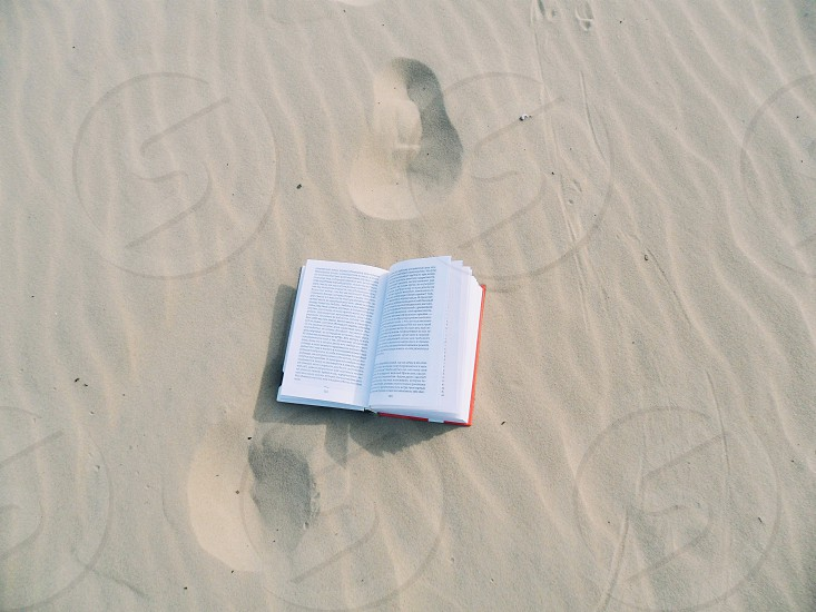 red book on white soft sand photo