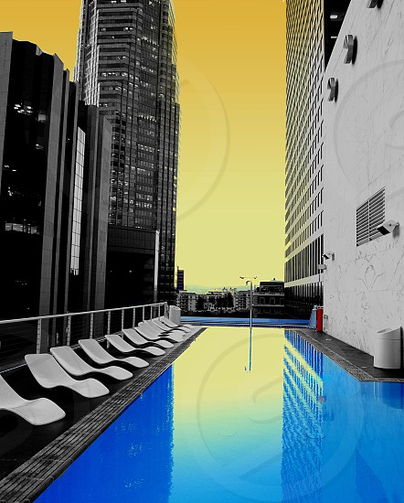 lounger chairs beside pool on high-rise building beside tower buildings photo