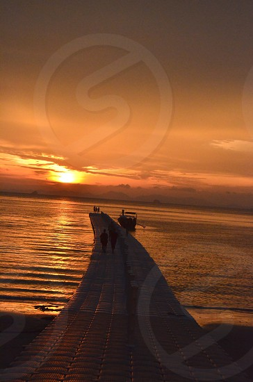 silhouette photography of person walking on dock during golden hour photo
