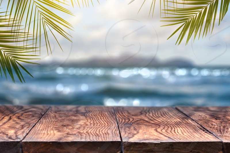 Landscape view with old wood table top and coconut leaf over blurred blue sea and white sand beach with clear blue sky background . Concept Summer Relax and Party. photo
