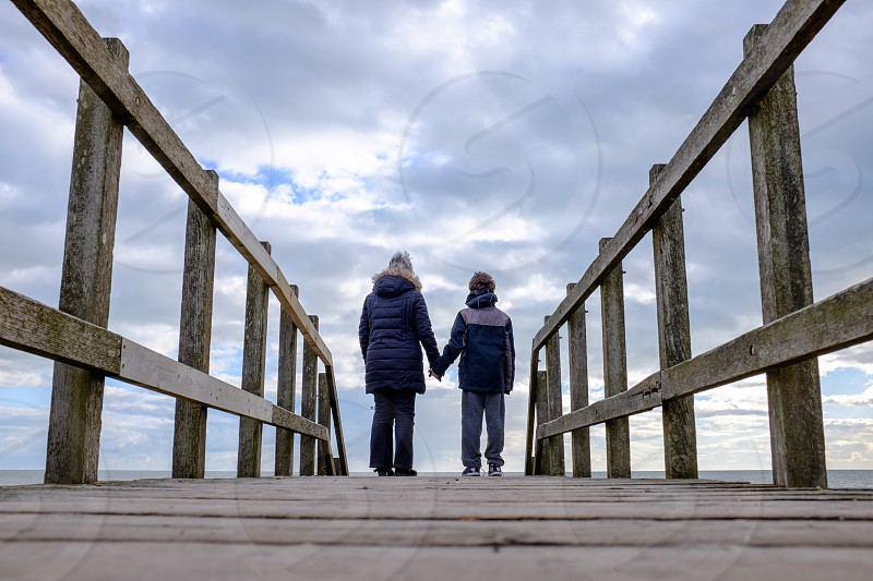 Back view of a Granny and Grandson holding hands on a wooden walkway looking out to sea with a big sky behind photo