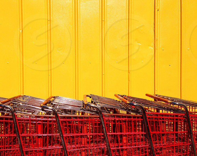 Red shopping carts are lined up near a yellow wall. photo