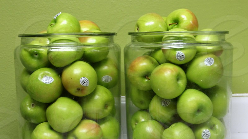 Green apples in two glass containers photo