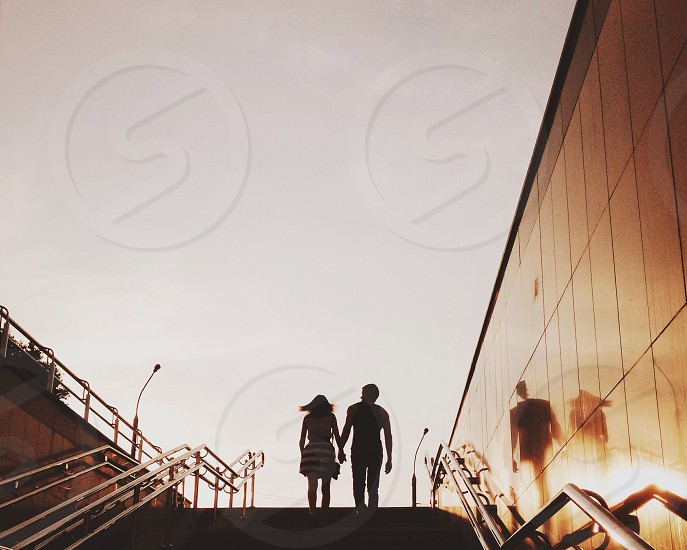 couple climbing up stairs holding hands during sunset photo
