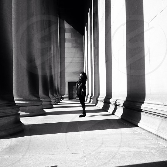 woman standing in shadow of pillars photo