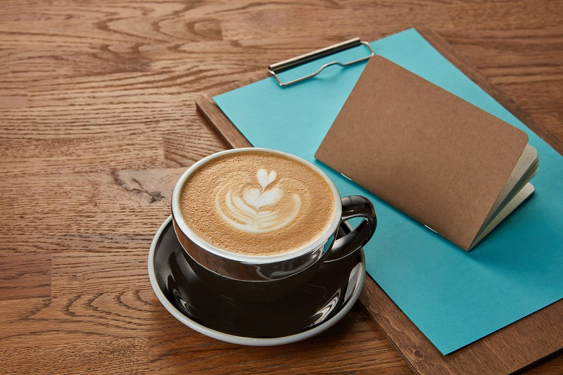Cup of coffee represented on wooden table with notebook and clipboard near. Delicious cappuccino coffee with milk. photo