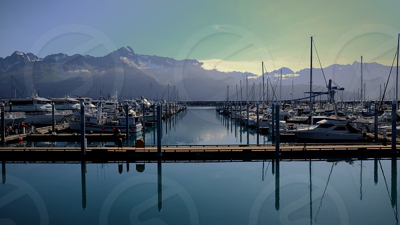 brown and white wooden pier in front of snowcap mountain under grey and white sky during day time photo